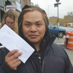 """""""I hope things get better,"""" said worker Nelson Aquino, holding up one of the checks he said he is owed."""