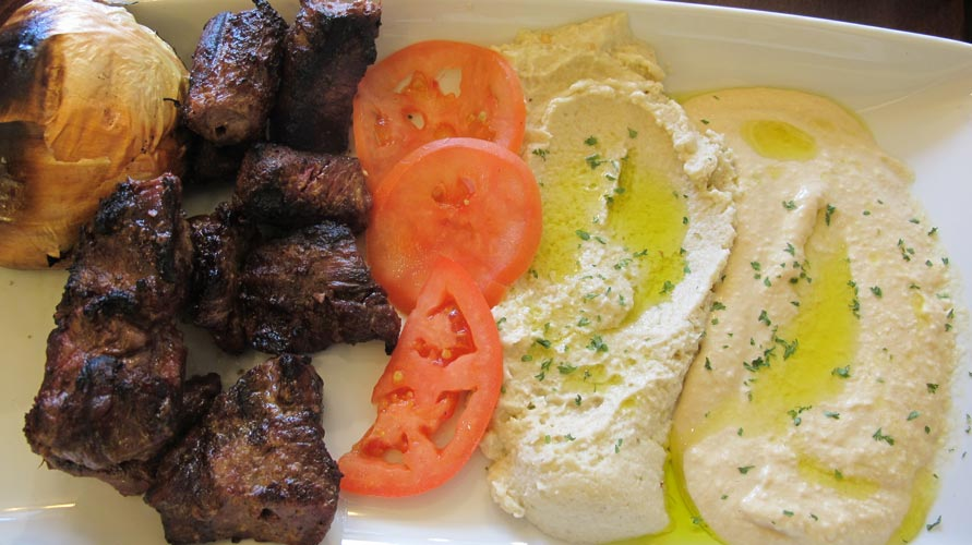 The plates are served with hummus, vegetables and freshly grilled meats.