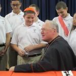Cardinal Dolan listened to students' essays on the importance of faith.