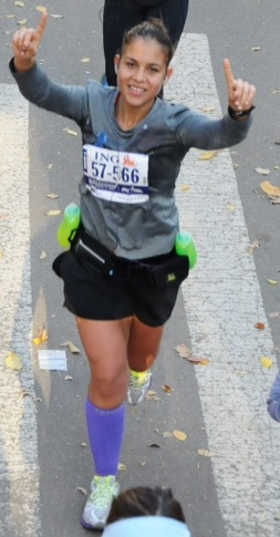 Runner Emerita Torres, who competed on behalf of BronxWorks, crosses the finish line at the 2013 ING New York City Marathon.