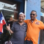 "Bertico Estilo (left) with his friend is a barber. ""This is a day very dear to us. I'm very proud of my country and my beautiful island."""