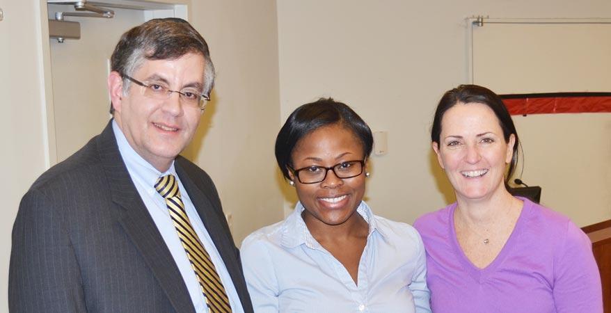 El Dr. Zvi Loewy, decano interino de la escuela de farmacia y la Dra. Maureen Sullivan, presidenta del Departamento de Farmacia Práctica felicitan a Tiffany Murray (centro), recipiente de la beca 'CVS Caremark Charitable Trust Pharmacy'.