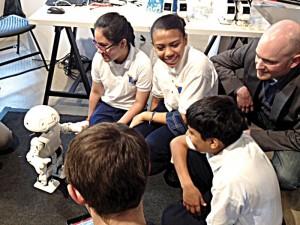 Los estudiantes y Johnson observan un robot en acción.