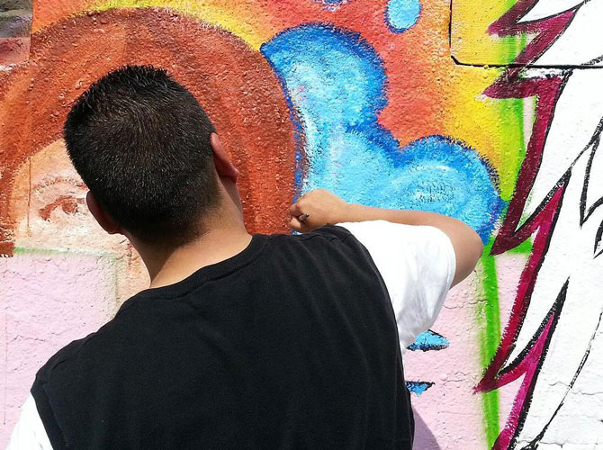 Santiago's canvas paintings incorporate graffiti elements.