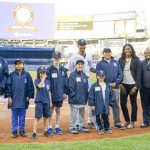 On the field at Yankee Stadium with New York Yankees player Chris Young (back row, center) and Con Edison representatives Johari Jenkins and Andres Ledesma (far right).