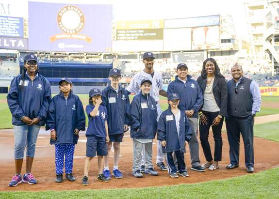 En el campo en el estadio de los Yankees con el jugador de los Yankees Nueva York Chris Young (última fila, centro) y los representantes de Con Edison Johari Jenkins y Andrés Ledesma (a la derecha).