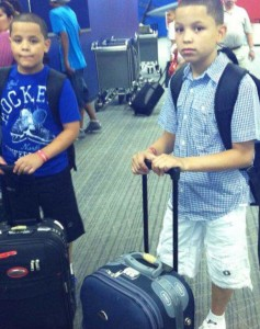 "Christopher (right) and his younger brother Jesslyn at the airport, ready to travel for a summer's vacation in the Dominican Republic. ""We went all the time to be with our family,"" says Dayanira."