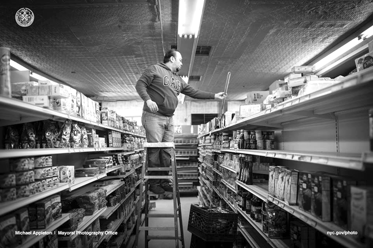 Abdullah Ferdous, who works as an electrician, changes a lighting fixture at a food market in Brooklyn.