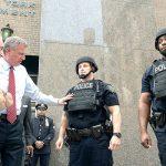 Commissioner William Bratton and Mayor Bill de Blasio inspect vests.
