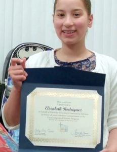 The fifth grader holds her certificate of recognition.