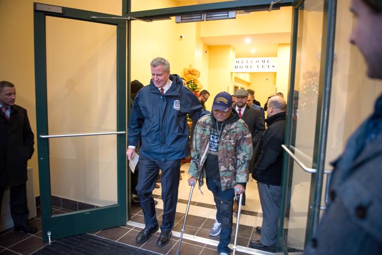 Mayor Bill de Blasio escorts veteran Samuel Rosado (left) into his new home.