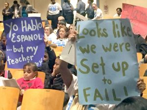Attendees held up signs during the meeting.
