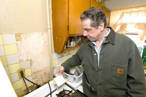 Cuomo holds a broken tile. Photo: Office of the Governor