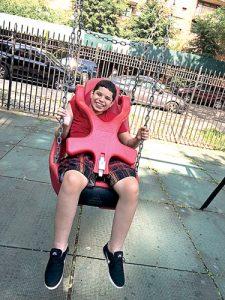 El hijo de Martínez, Adrián, está paralizado de la cintura para abajo. Aquí, se balancea en el parque frente a la nueva unidad de la familia.