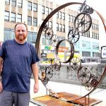 Artist and welder Colin Nicodemo stands next to his sculpture, All Roads Lead to Fordham, on the Grand Concourse.