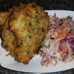 Tome un plato de pasteles de bacalao con ensalada de col con lima y cilantro.