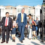 Carranza, with Mayor de Blasio, walks a student in on the first day of school.