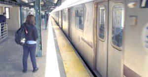Mujer en la plataforma del metro como tren se detiene